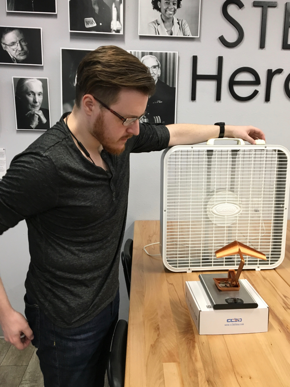 Photo of Rich standing with his hand on the box fan that is blowing on a 3D printed model of WWII wing which is sitting on a postal scale.