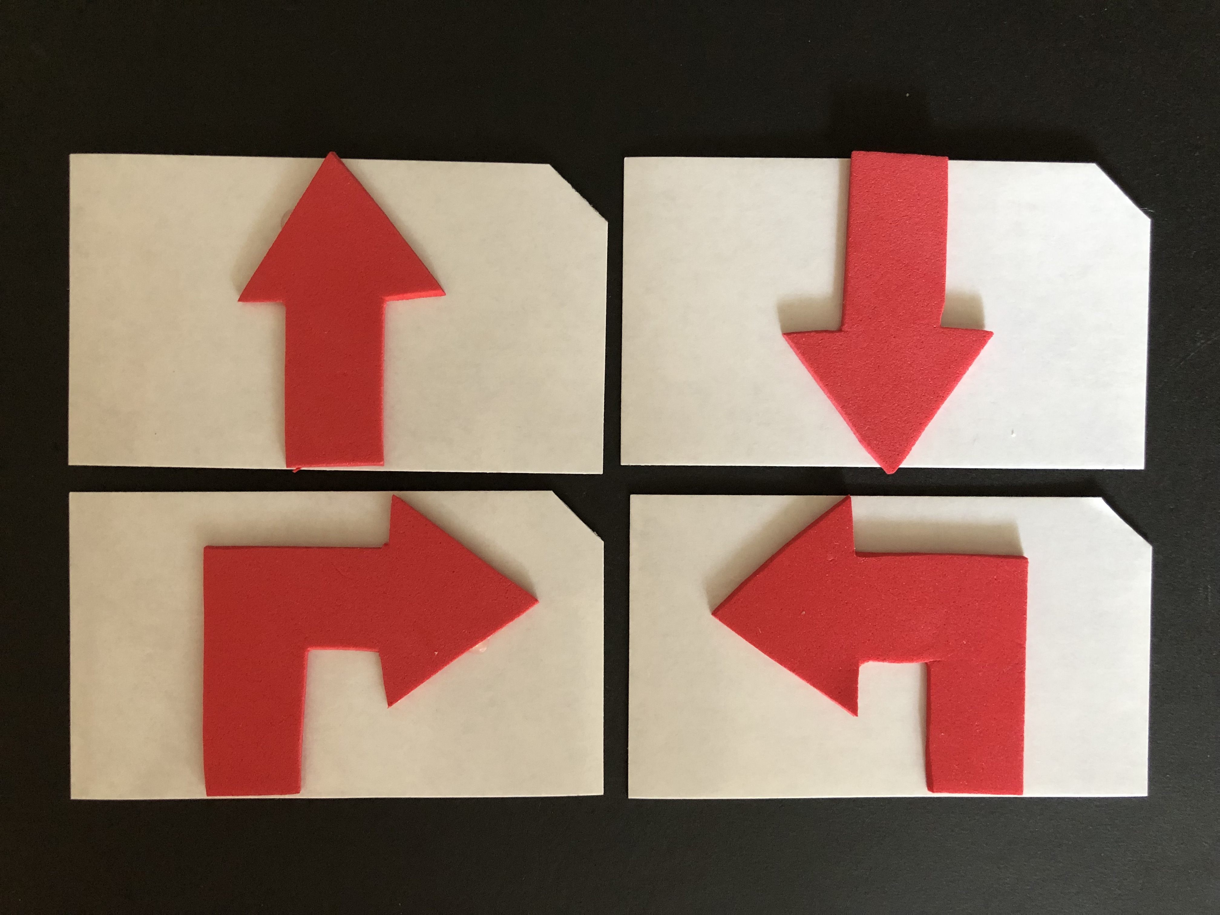 Four magnetic business cards with clipped top right corners. Each card has one red foam arrow: up, down, right or left.
