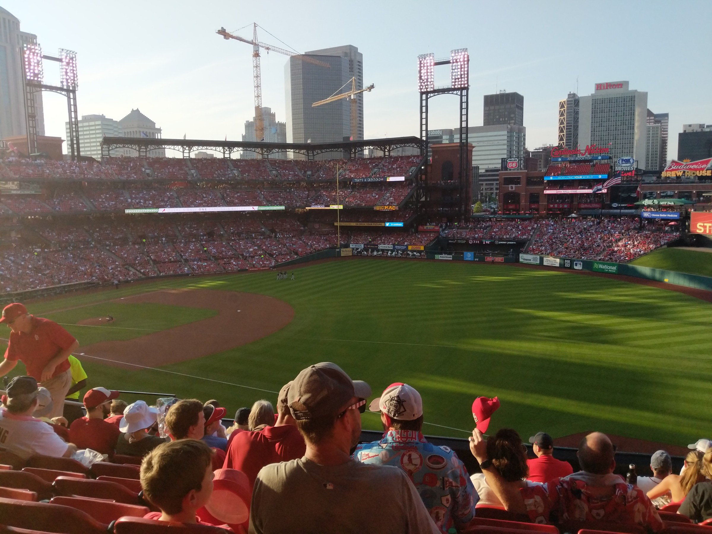 Photo taken from the stands showing a baseball field, crowded stands, and high-rise buildings in the background.