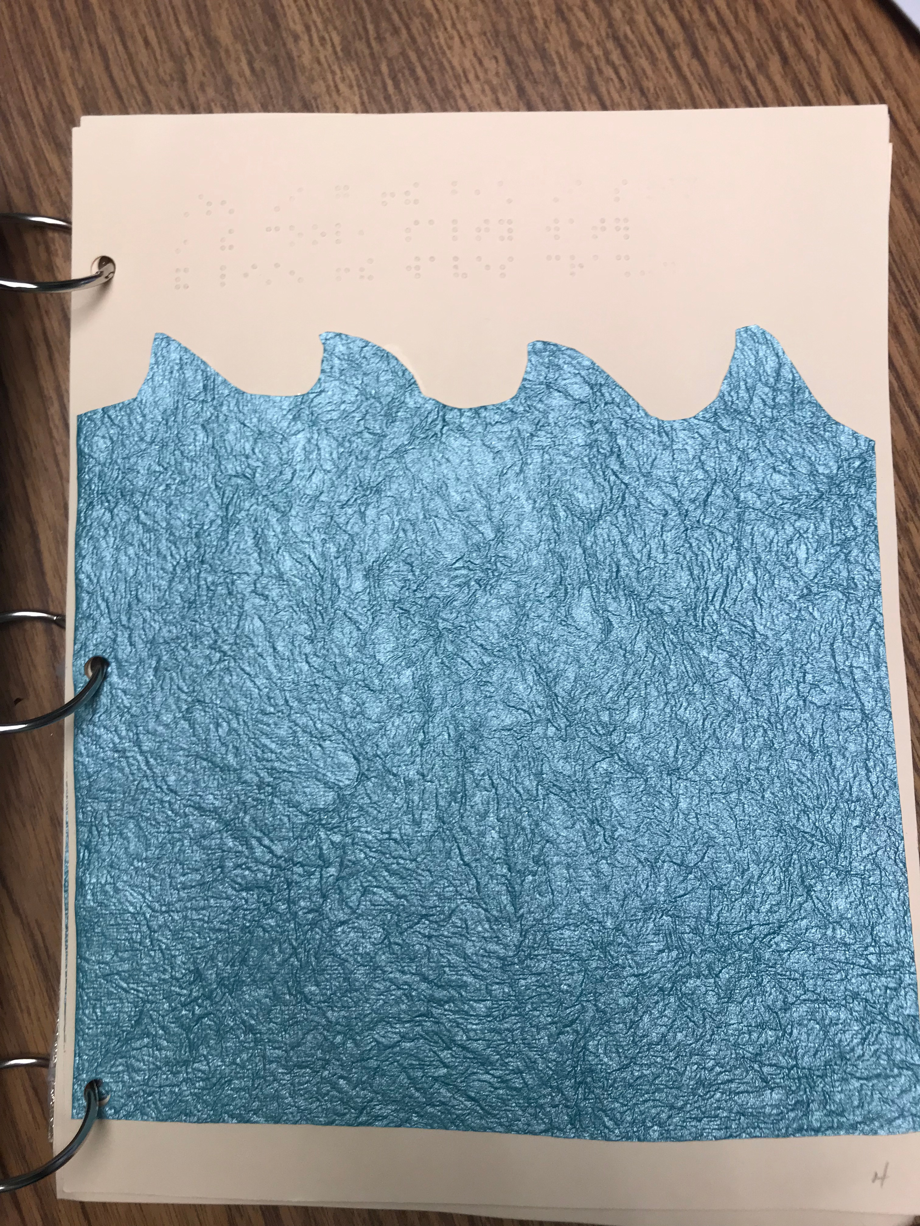 Blue wrinkled textured paper cut into waves