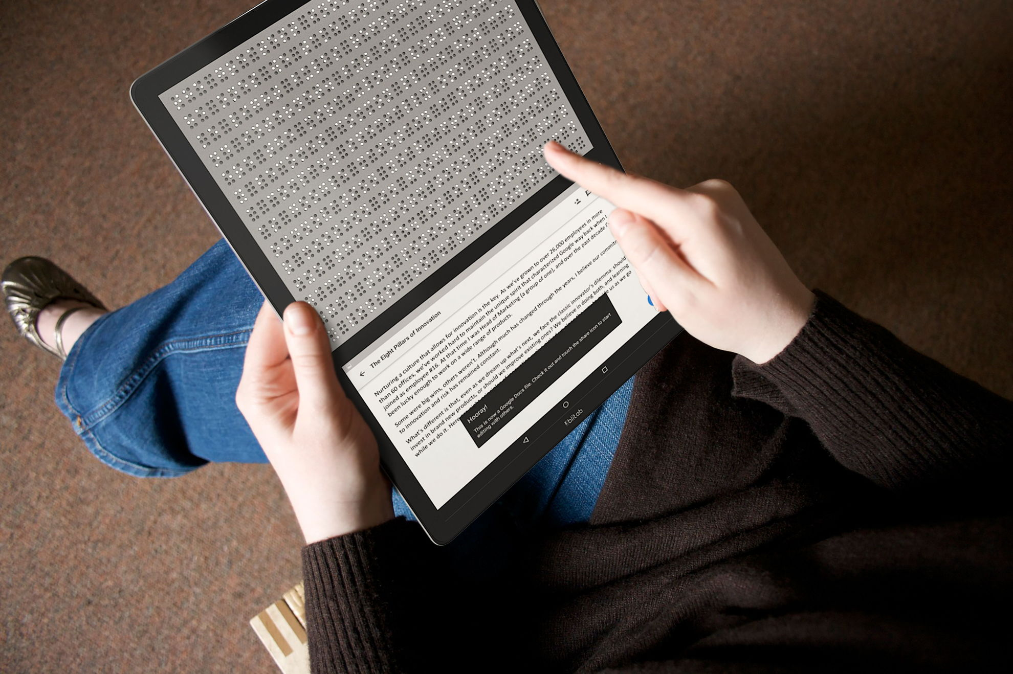 Woman holding Blitab in her lap reading a Google Document in braille with the print displayed at the bottom of the device.