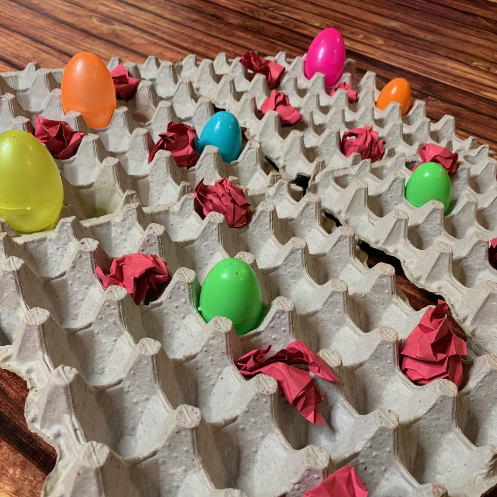 Egg carton flats with randomly placed colorful Easter eggs and wadded construction paper (lava rocks).