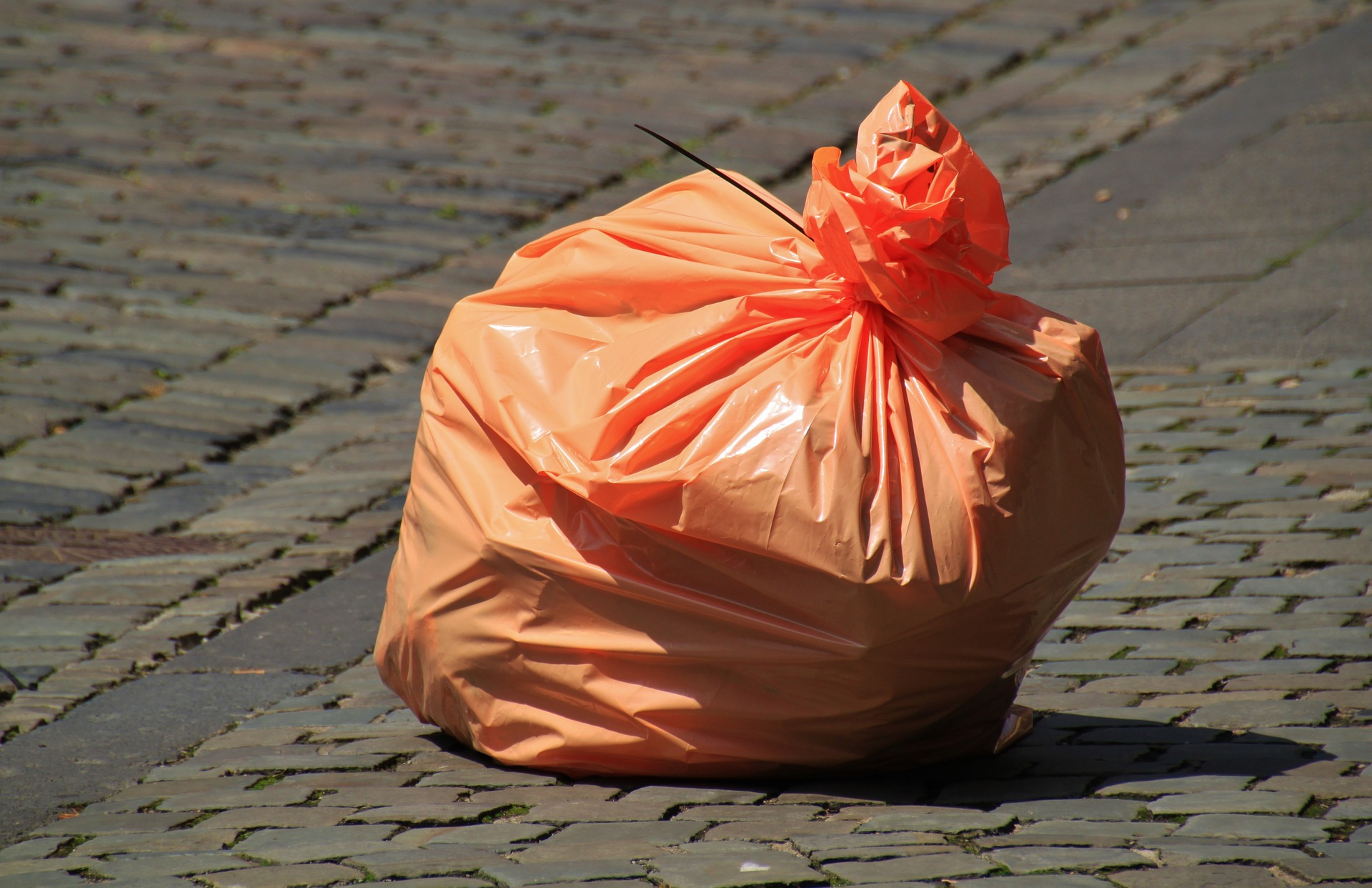 Filled orange garbage bag.