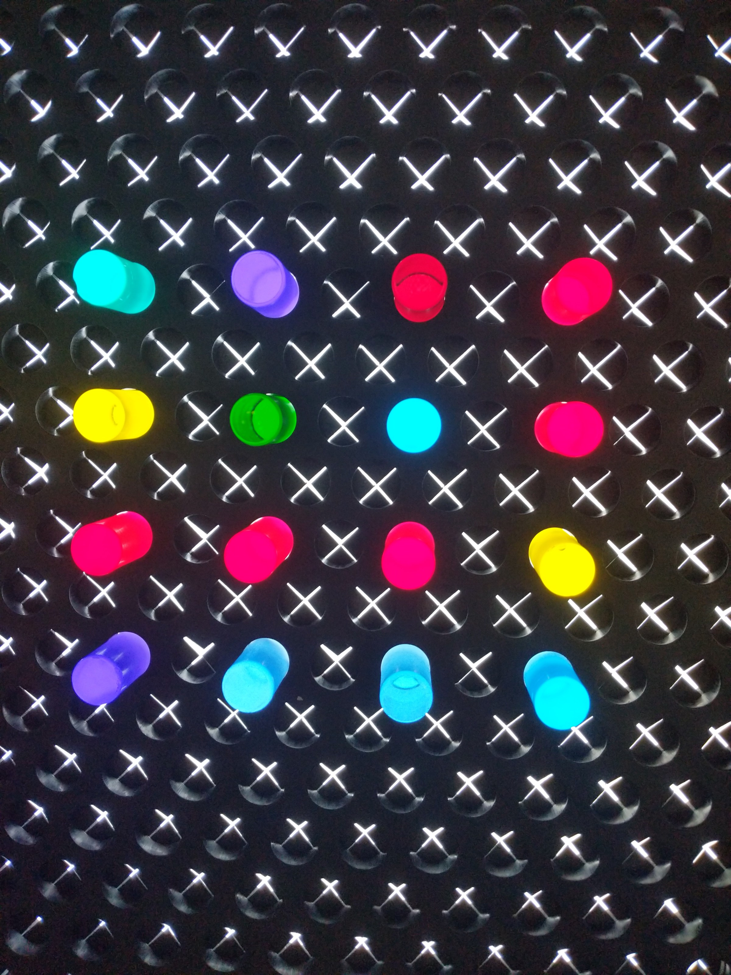 Image of an activity with a black background, lights and what appears to be colorful, lit pegs.