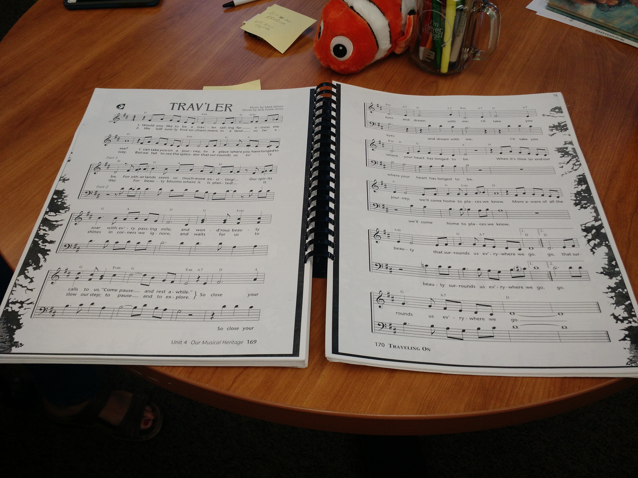 an 11x14 spiral bound book with music on a table.