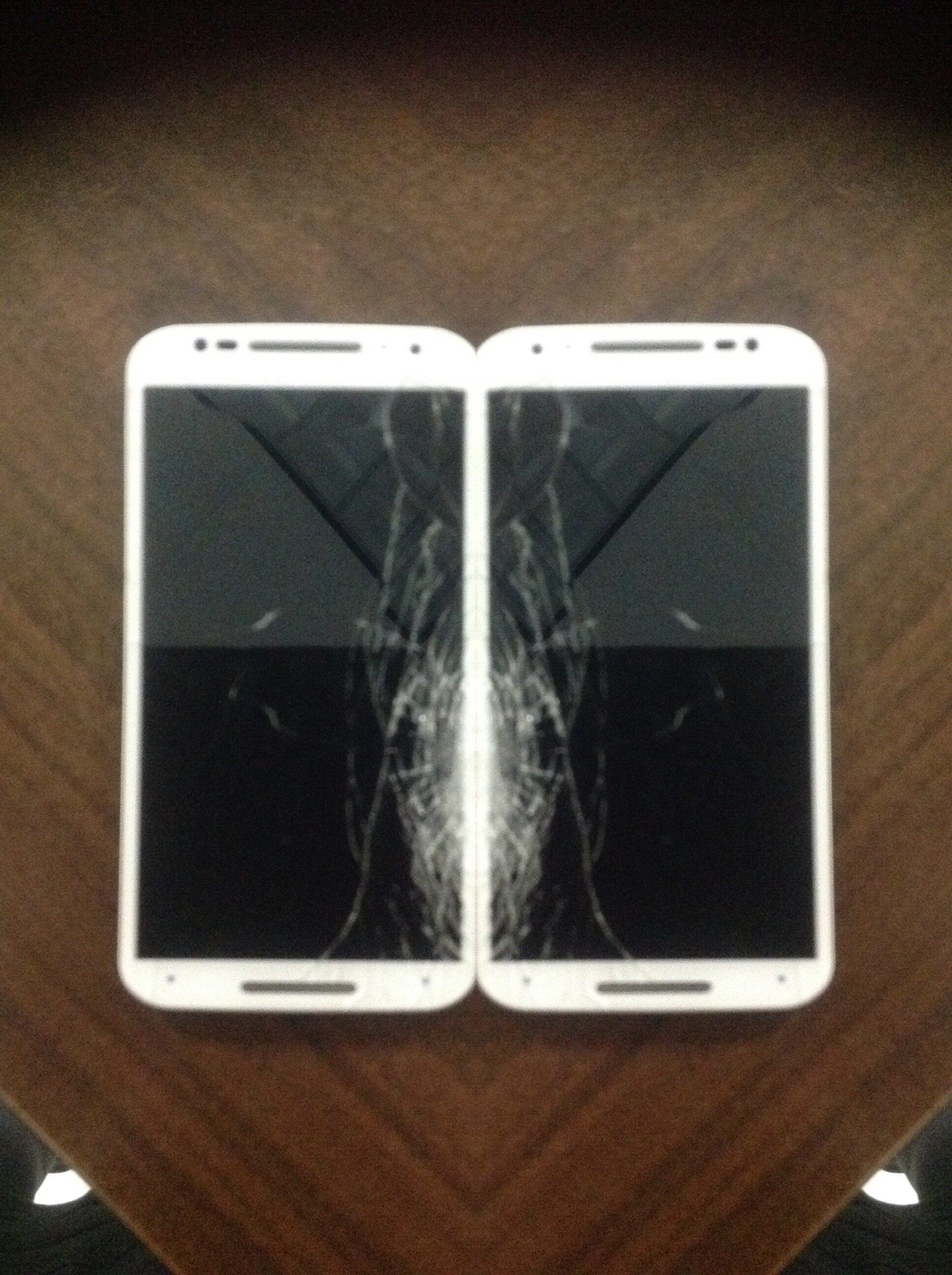 A double image of a white phone with a cracked screen; phones are mirrored image side-by-side.