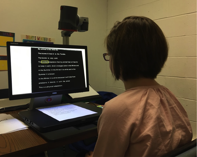 "Photograph of a student viewing her biome script on the screen of the video magnifier that has a black background with white print. The word ""coolest"" is outlined in yellow as it is read aloud."