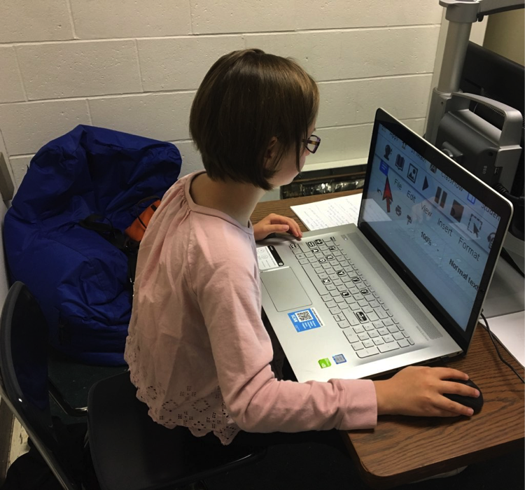 Photograph of a student sitting at a table using a large screen laptop with screen magnification software. The laptop screen is magnified to view a Read & Write Google toolbar and a large red arrow pointer.
