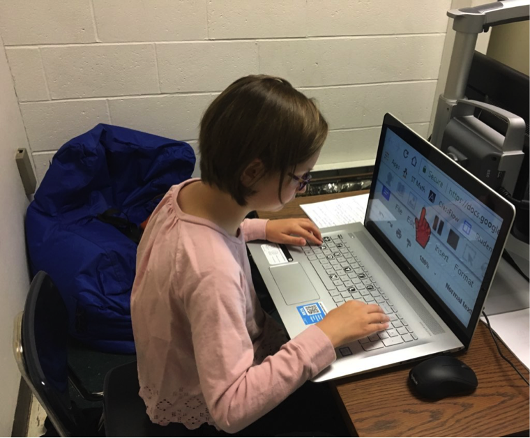 Photograph of a student sitting at a table using a large screen laptop with screen magnification software. The student uses keyboard shortcuts to magnify the toolbar to view the play, stop, and pause buttons and a red point to activate the play button to read aloud her work.