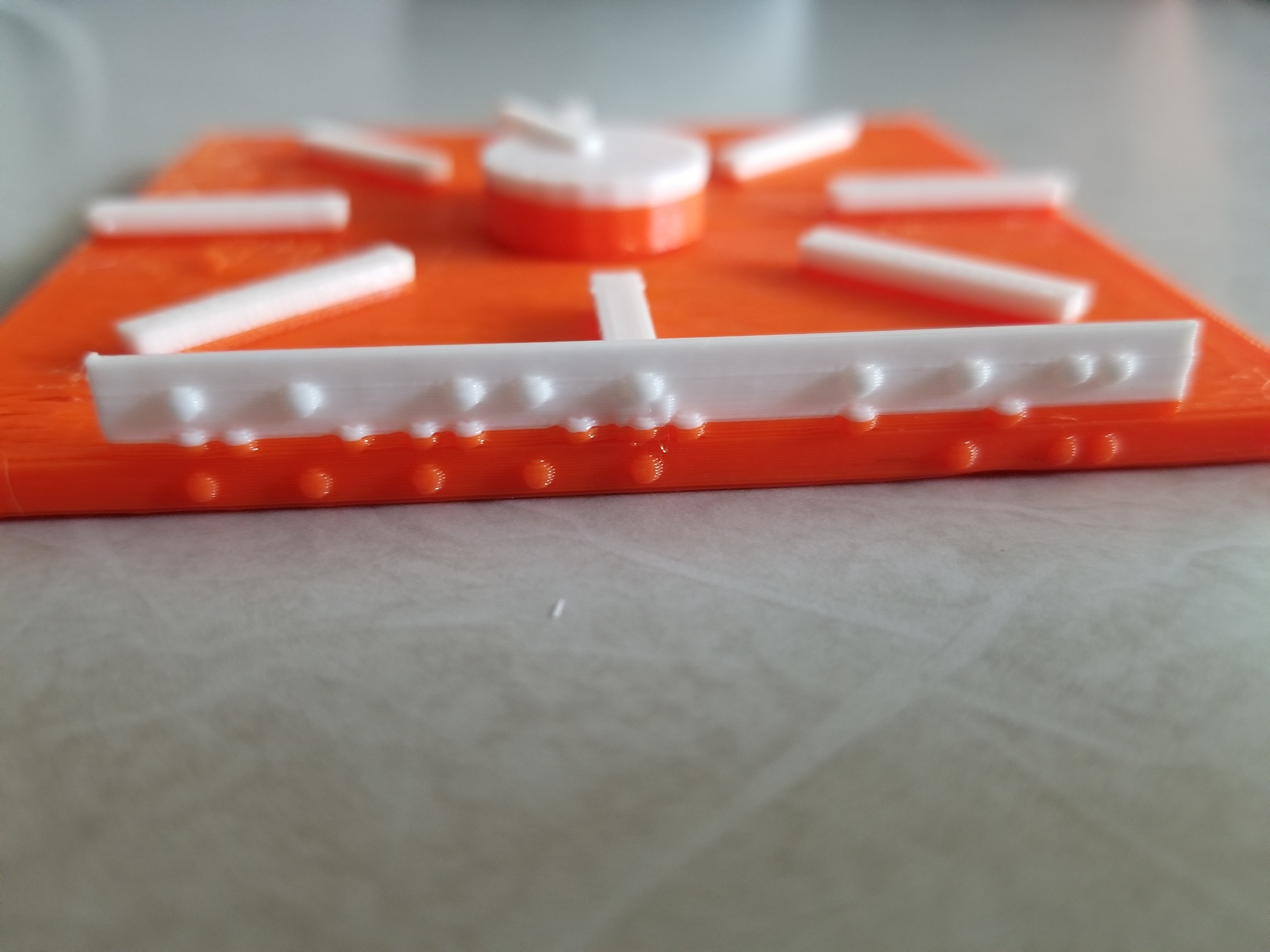 "Photo: front view of 3D printed virtual rotor showing 1/4"" base and braille dots that spell 'rotor box'."