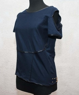 Dark blue silky short sleeve blouse with raised gold bumps creating a braille label at the bottom, left side of the blouse.