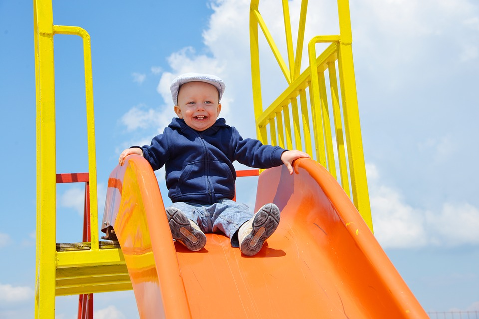 Smiling toddler wearing a hat sitting at the top of bright orange slid on a sunny day.