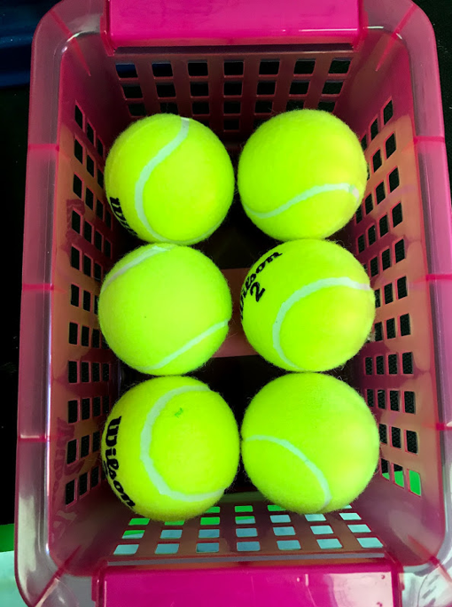 six tennis balls stored in a plastic basket.