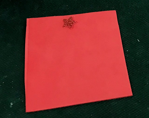 Large red foam square with a tactile sparkly star for orientation at the top center. The student will press the Specdrum ring to the square to hear the game directions.