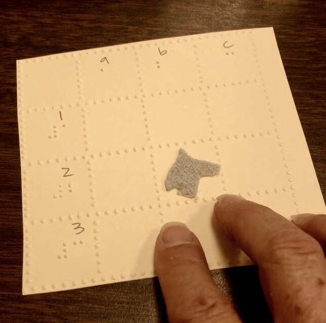 Photo of a 3x3 braille grid on a braille paper with rows 1,2 3 and columns A,B,C and a tactile horse head in the square at row two 2 column B.