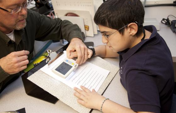 Student with low vision holds magnifier