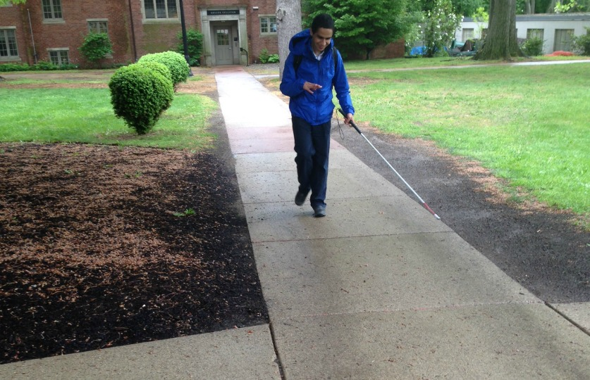 Student walks with cane along sidewalk